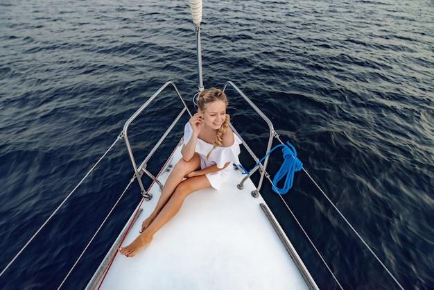 Lächelnde reizvolle frau der junge im weißen sommerkleid, das an der weißen luxusyacht sich entspannt.