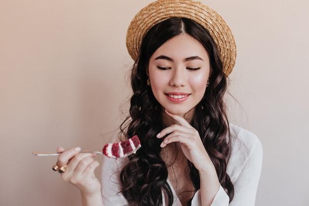 Lächelnde romantische asiatische frau, die kuchen isst. elegante lockige frau, die nachtisch genießt.