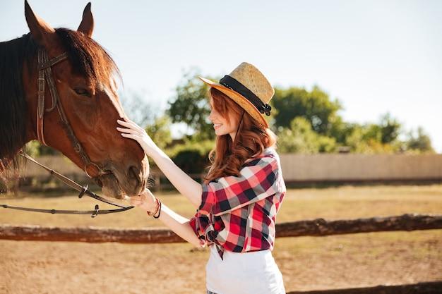 Lächelnde rothaarige junge frau cowgirl, die sich um ihr pferd auf der farm kümmert