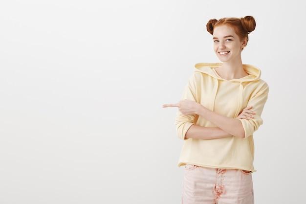 Lächelnde rothaarige teenagerin zeigt mit dem finger nach links
