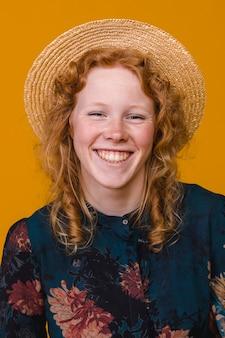 Lächelnde rothaarigefrau im studio mit hellem hintergrund