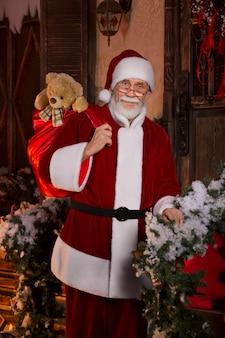 Lächelnde santa claus, die eine tasche mit geschenken hält