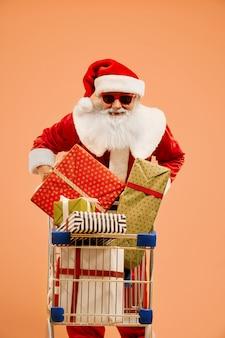 Lächelnde santa claus, die warenkorb mit geschenkboxen drückt