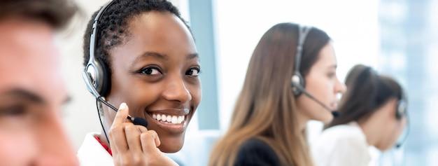 Lächelnde schöne afroamerikanerfrau, die im kundenkontaktcenter mit verschiedenem team arbeitet