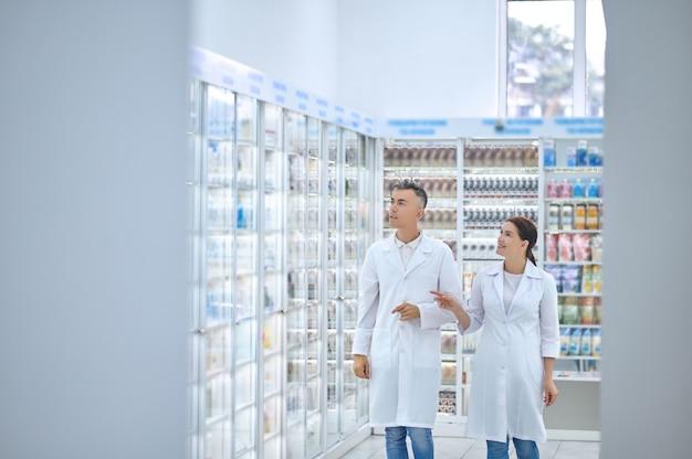 Lächelnde schöne apothekerin zeigt auf die vitrine mit medikamenten zu ihrem ernsten männlichen kollegen