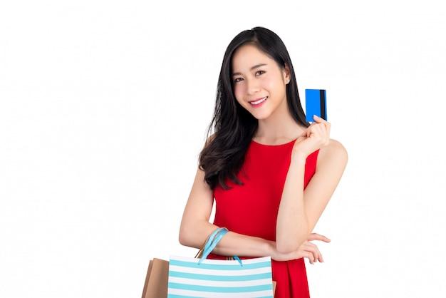 Lächelnde schöne asiatin der junge, die in der hand kreditkarte darstellt