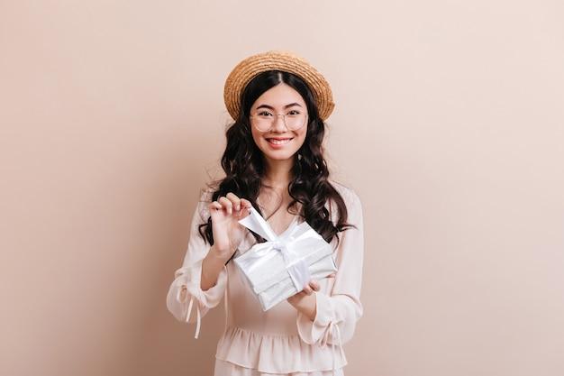 Lächelnde schöne asiatische frau, die geburtstagsgeschenk öffnet. vorderansicht der glücklichen japanischen frau mit geschenk, das strohhut trägt.