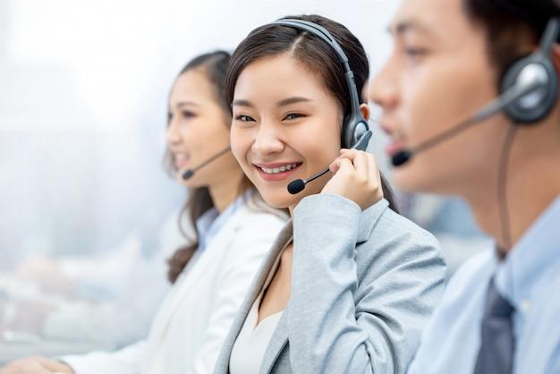 Lächelnde schöne asiatische frau, die im kundenkontaktcenterbüro arbeitet