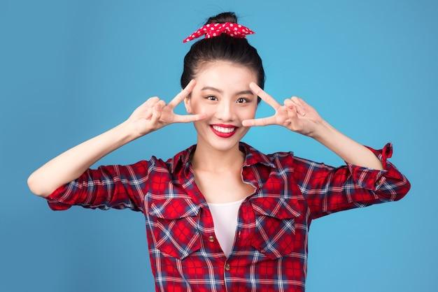 Lächelnde schöne asiatische frau im pin-up-stil kleid über blau gekleidet.