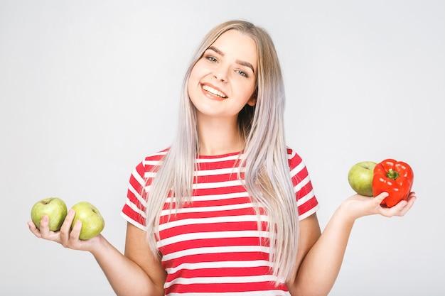 Lächelnde schöne blonde frau, die vegane lebensmittelzutaten hält. isoliertes porträt auf weiß.