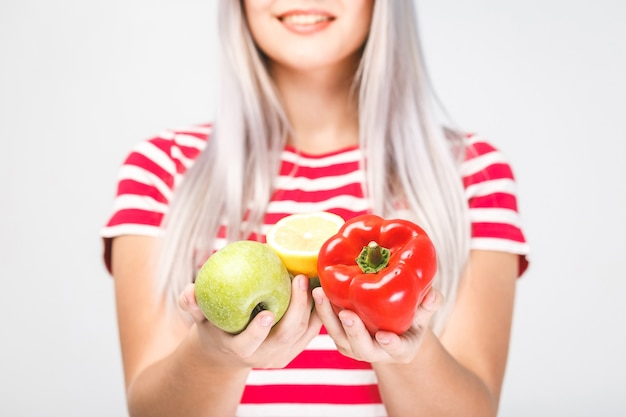 Lächelnde schöne blonde frau, die vegane lebensmittelzutaten hält. isoliertes porträt auf weiß. Premium Fotos