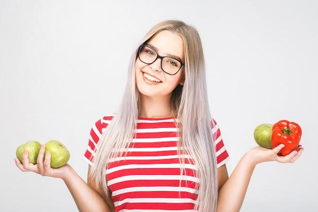 Lächelnde schöne blonde frau, die vegane lebensmittelzutaten hält