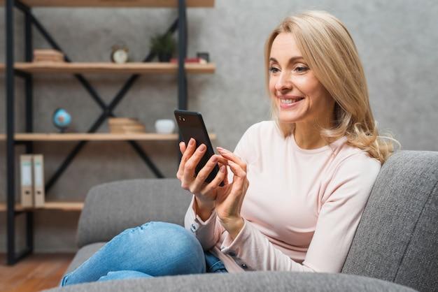 Lächelnde schöne blonde junge frau, die auf sofa unter verwendung des intelligenten telefons sitzt