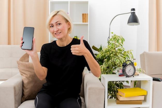 Lächelnde schöne blonde russische frau sitzt auf sessel, der telefon und daumen hoch im wohnzimmer hält