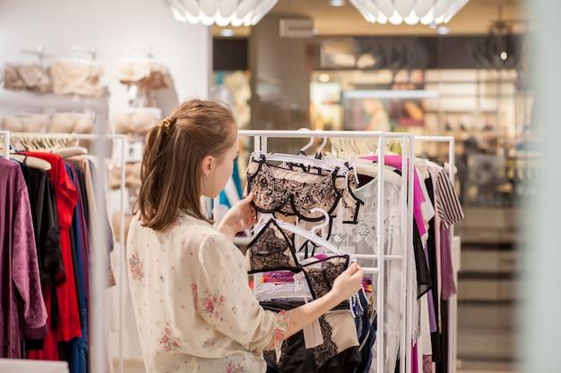 Lächelnde schöne brünette, die bikini wählt, während sie im laden steht.