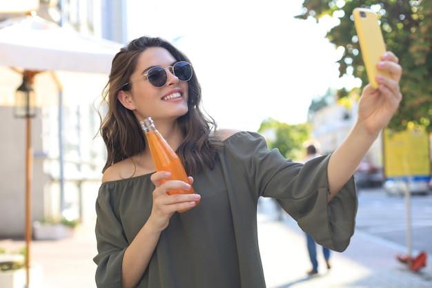 Lächelnde schöne brünette frau, die draußen auf der straße spazieren geht, selfie mit dem handy machen und saft trinken.