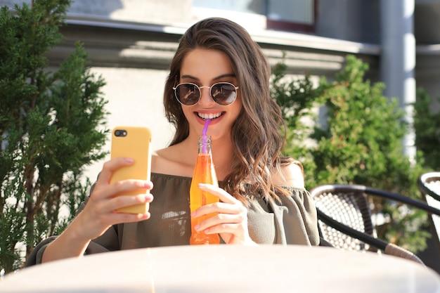 Lächelnde schöne brünette frau, die im straßensommercafé sitzt, selfie mit dem handy machen und saft trinken.