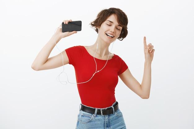 Lächelnde schöne brünette frau, die sorglos tanzt, musik hört und in kopfhörern tanzt, smartphone hält