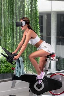 Lächelnde schöne brünette mit langen haaren in einem weißen netzoberteil und weißen kurzen shorts, die im profil posieren, während sie auf einem heimtrainer in einem geräumigen fitnessstudio für sport sitzen. virtual-reality-brille.