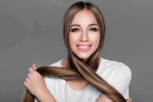 Lächelnde schöne brunettefrau mit dem glänzenden geraden langen haar. pflege der haare