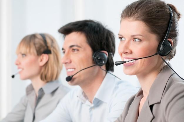 Lächelnde schöne dame, die am callcenter mit kollegen im büro arbeitet