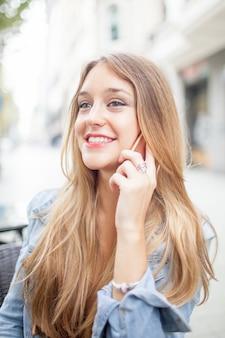 Lächelnde schöne dame, die draußen am telefon spricht