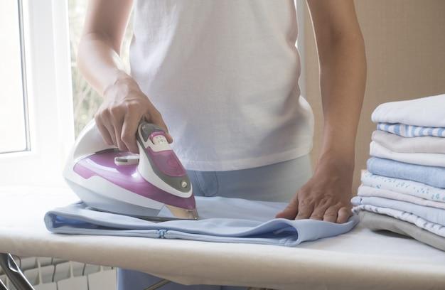 Lächelnde schöne dunkelhäutige brünette frau im weißen t-shirt bügelt blauen rock auf einem bügelb...
