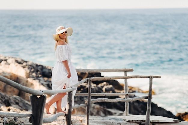 Lächelnde schöne frau am strand in einem strohhut auf der insel zakynthos. ein mädchen in einem weißen kleid bei sonnenuntergang auf zakynthos-insel, griechenland