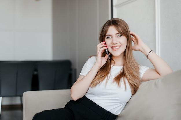 Lächelnde schöne frau, die am telefon spricht, das auf einer couch zu hause sitzt