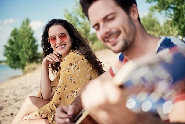 Lächelnde schöne frau, die auf einer decke am strand sitzt