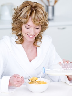 Lächelnde schöne frau, die cornflakes am morgen isst - drinnen