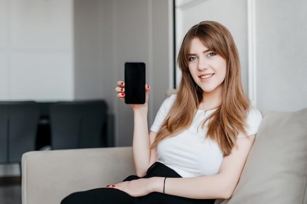 Lächelnde schöne frau, die leeren kopienraum-telefonbildschirm zeigt, der auf einer couch zu hause in der modernen wohnung sitzt