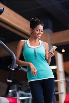 Lächelnde schöne frau, die smartphone im fitness-studio verwendet