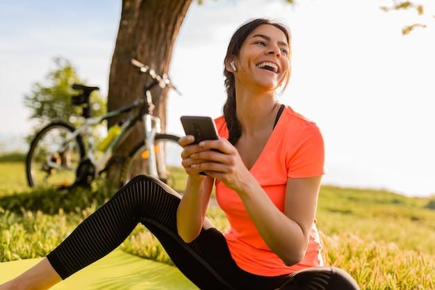Lächelnde schöne frau, die telefon hält, das sport am morgen im park tut