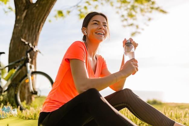 Lächelnde schöne frau, die wasser in der flasche trinkt, die sport am morgen im park tut