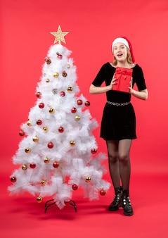 Lächelnde schöne frau im schwarzen kleid und im weihnachtsmannhut, der nahe weißem neujahrsbaum steht und geschenk auf rot hält
