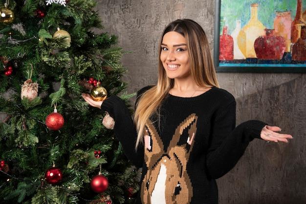 Lächelnde schöne frau im warmen pullover, der mit händen nahe weihnachtsbaum aufwirft. hochwertiges foto