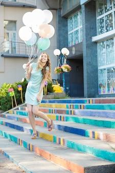 Lächelnde schöne frau mit fliegenden bunten luftballons in der stadt