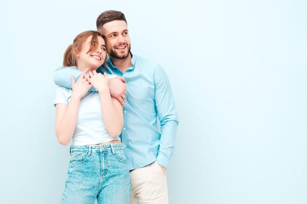 Lächelnde schöne frau und ihr hübscher freund. fröhliche fröhliche familie mit zarten momenten in der nähe der hellblauen wand im studio