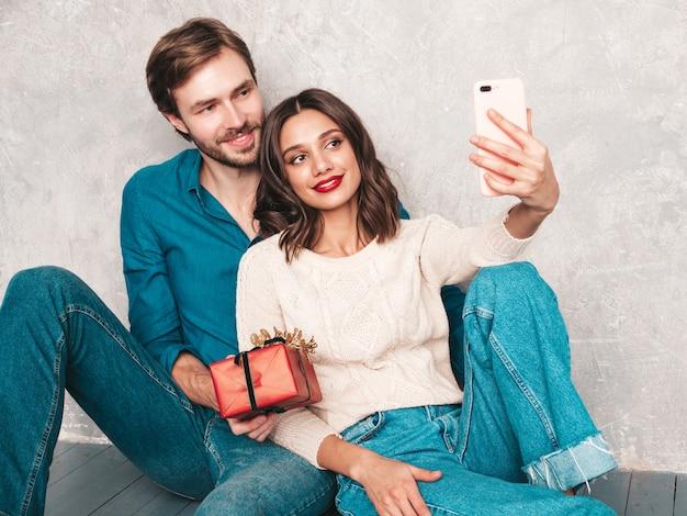 Lächelnde schöne frau und ihr hübscher freund. glückliche fröhliche familie, die nahe grauer wand aufwirft. valentinstag. modelle umarmen und geben seiner freundin geschenkbox.