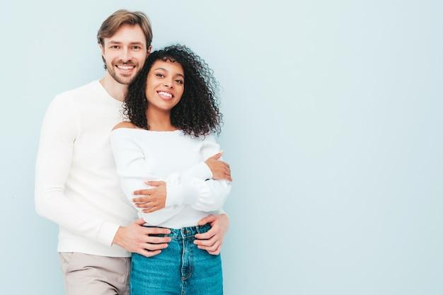 Lächelnde schöne frau und ihr hübscher freund. glückliche fröhliche gemischtrassige familie mit zarten momenten auf grau