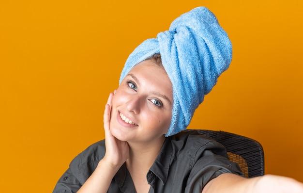 Lächelnde schöne frau wickelte haare in handtuch, die selfie machten und hand auf wange legten