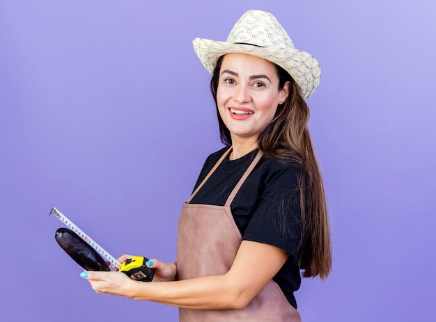 Lächelnde schöne gärtnerin in uniform mit gartenhut, die auberginen mit maßband auf blau isoliert misst