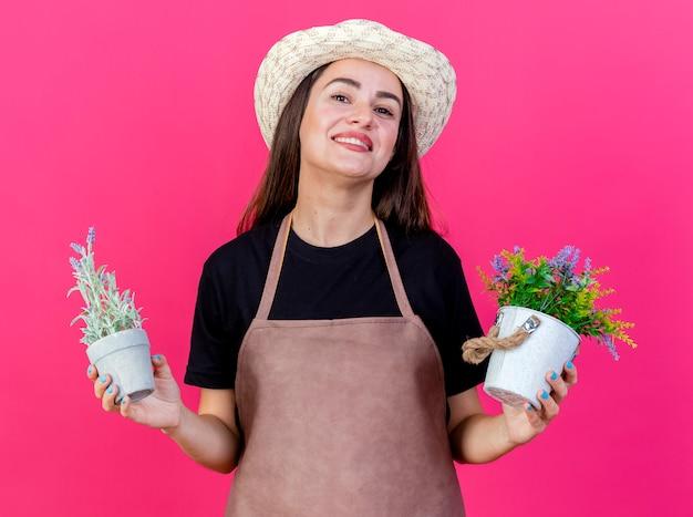 Lächelnde schöne gärtnerin in uniform mit gartenhut, die blume im blumentopf hält, lokalisiert auf rosa hintergrund