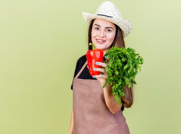 Lächelnde schöne gärtnerin in uniform mit gartenhut, die cliantro mit pfeffer an der kamera lokalisiert auf olivgrünem hintergrund heraushält