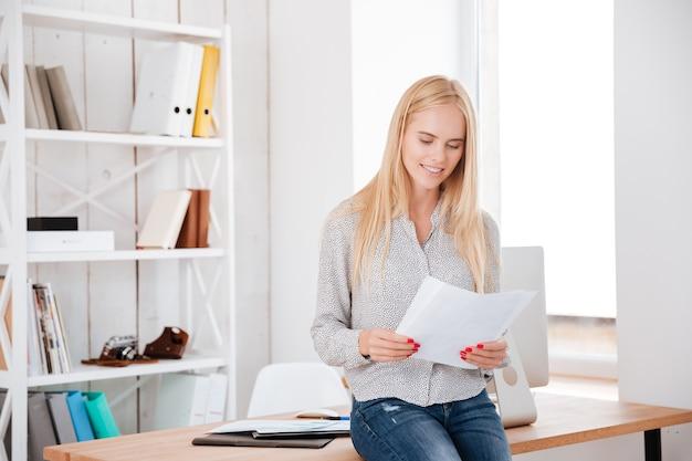 Lächelnde schöne geschäftsfrau, die auf dem schreibtisch sitzt und dokumente liest