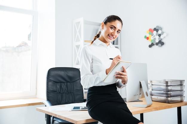 Lächelnde schöne geschäftsfrau, die auf dem schreibtisch sitzt und notizen macht
