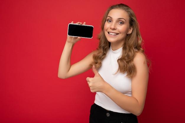 Lächelnde schöne junge blonde frau mit weißem t-shirt auf rotem hintergrund mit kopienraum