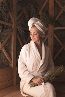 Lächelnde schöne junge frau, die auf bank an der sauna sitzt