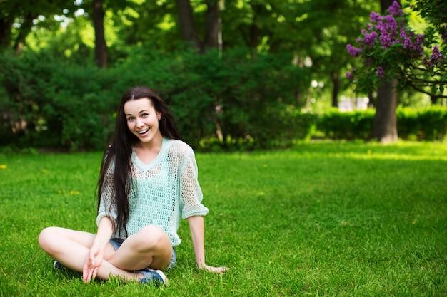 Lächelnde schöne junge frau, die auf gras sitzt, gegen grün des frühlingsparks.